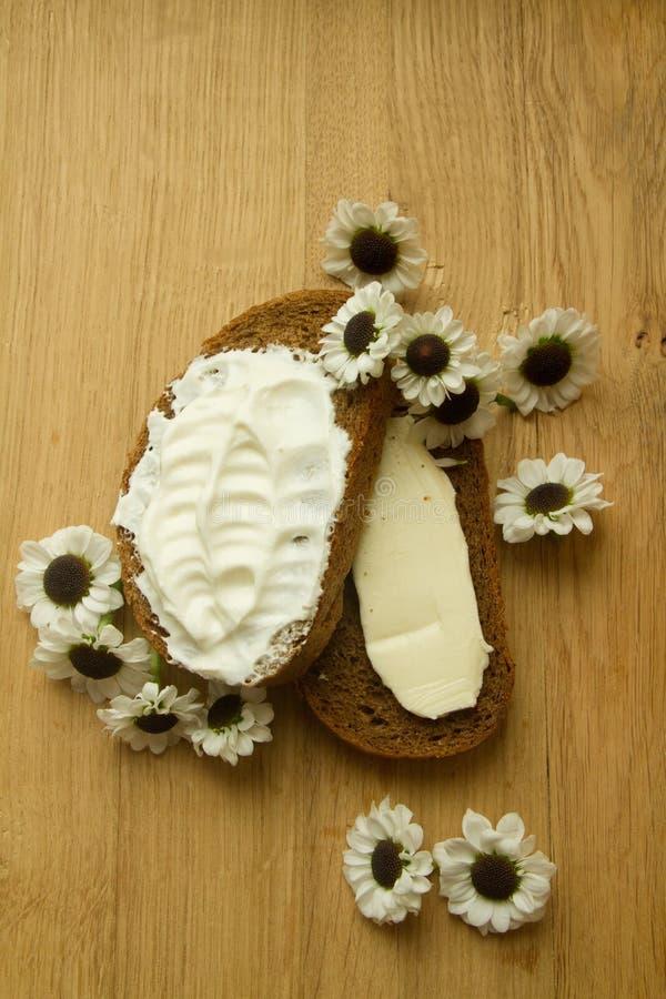 Stillleben mit Brot und Gänseblümchen auf einem Holztisch stockfotografie