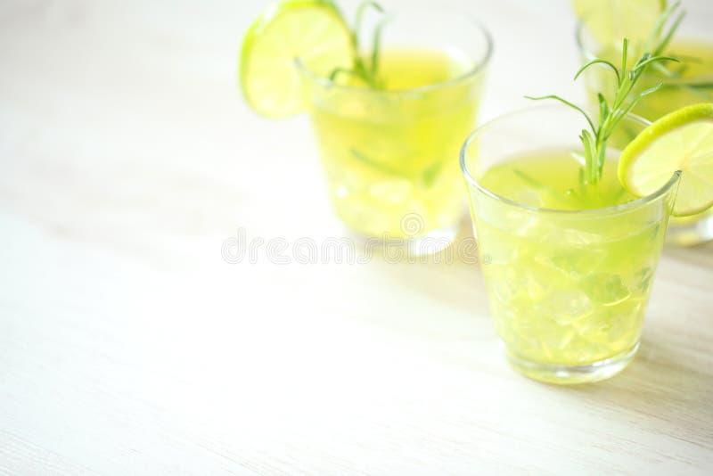 Stillleben mit bunten hellen Cocktails auf dem hölzernen Hintergrund, verziert mit Rosmarin und Kalk lizenzfreie stockfotografie