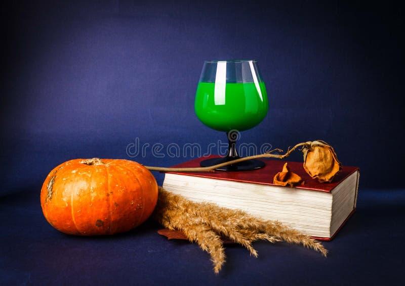 Stillleben mit den Rosafarbener und Halloweens Getränken des Kürbises, des Buches, lizenzfreies stockbild