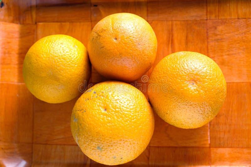 Stillleben mit drei reifen geschmackvollen Orangen auf braunem Behälter stockfotos