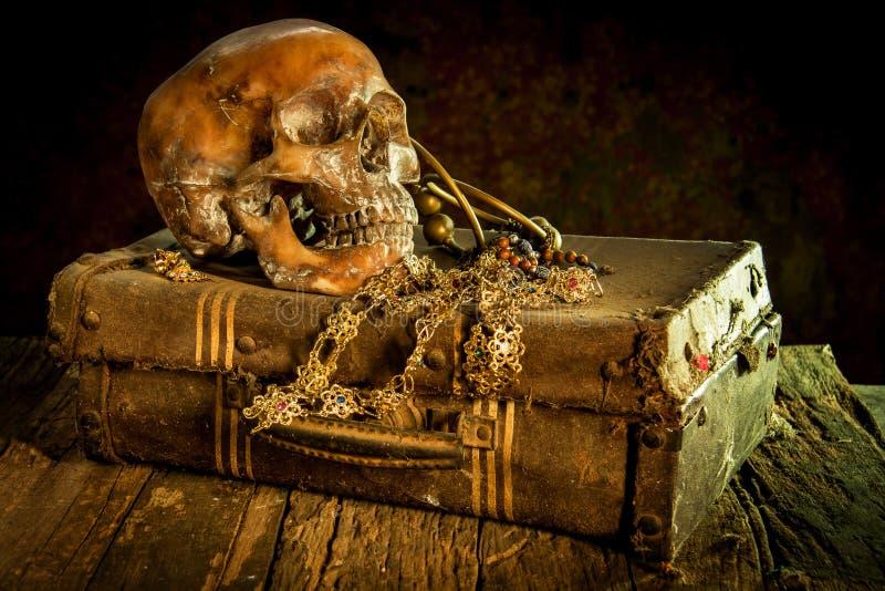 Stillleben mit einem menschlichen Schädel mit alter Schatztruhe und Gold, stockfotos