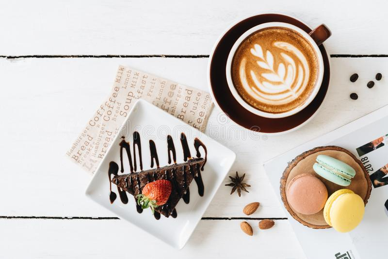 Stillleben mit einem Tasse Kaffee, einem Schokoladenkuchen und macarons auf der wei?en Tabelle stockbilder