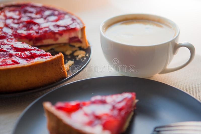 Stillleben mit einem Tasse Kaffee und einer Süßspeise mit Erdbeeren, Käsekuchenkuchen mit Scheiben von Beeren im Gelee auf die Ob lizenzfreie stockfotografie