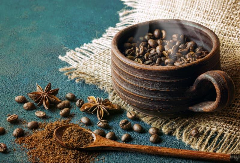Stillleben mit einer Lehmschale gefüllt mit Kaffeebohnen, Anissternen und hölzernem Löffel stockbilder