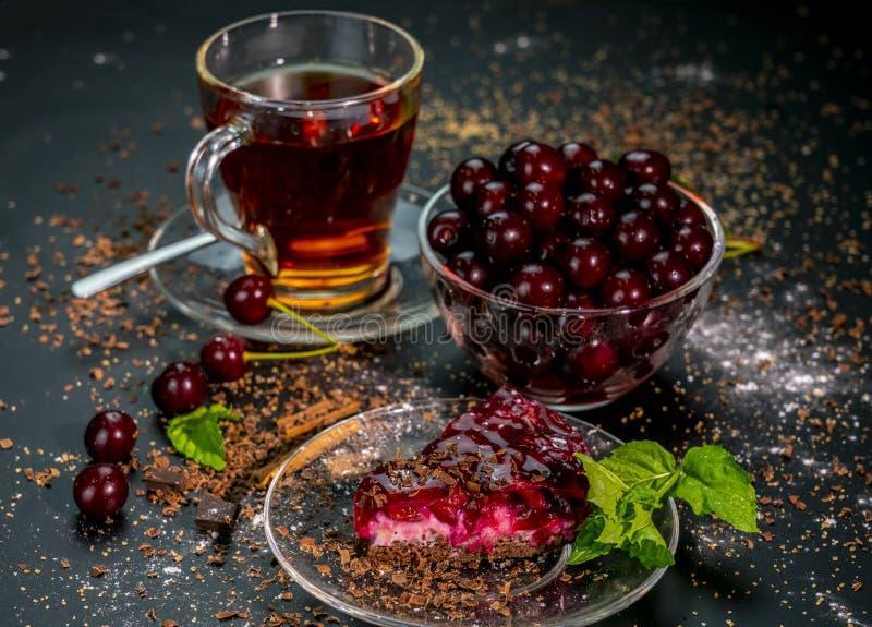 Stillleben mit einer Schale des starken Tees, der reifen Kirschen und des Kirschkuchens auf einem schwarzen Hintergrund lizenzfreie stockbilder