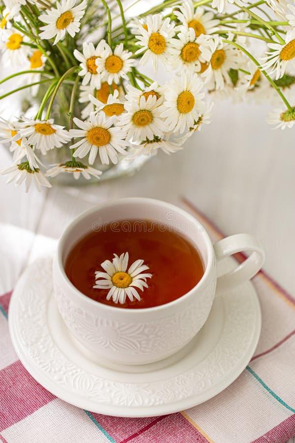 Stillleben mit einer Tasse Tee, Plätzchen und Gänseblümchen lizenzfreie stockfotografie