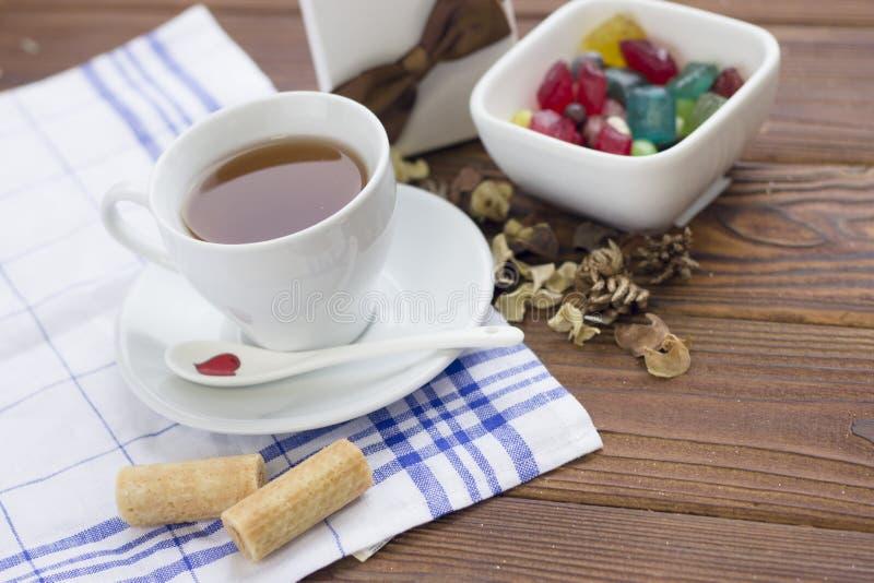 Stillleben mit einer Teeschale, Untertasse, Löffel, einer Schüssel Süßigkeiten und einer Geschenkbox stockfotos
