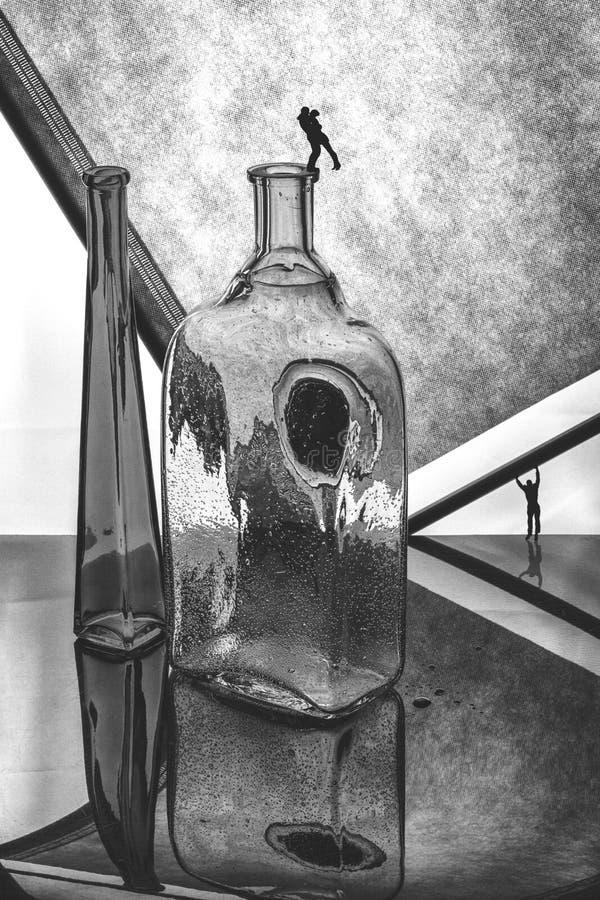 Stillleben mit Glasflaschen und Schattenbildern von Leuten Mädchen und Junge küssen im Garten stockfotografie