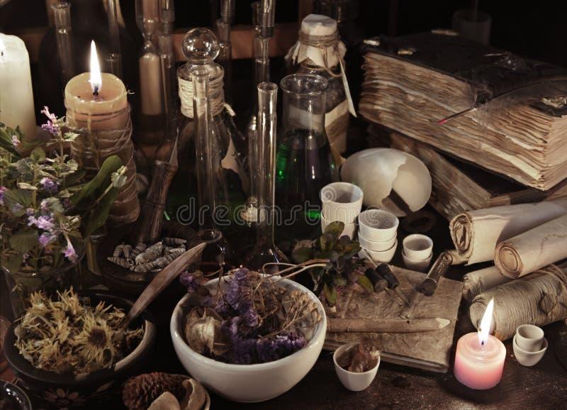 Stillleben mit Hexenbüchern, -rollen, -kräutern und -magie wendet ein stockbild