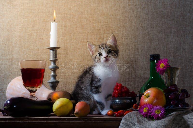 Stillleben mit Kätzchenkürbistraubenhunderosengrün-Flasche grap stockfoto