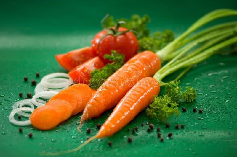 Stillleben mit Karotten mit gehackten Zwiebelringen, schwarzer Pfeffer lizenzfreies stockbild