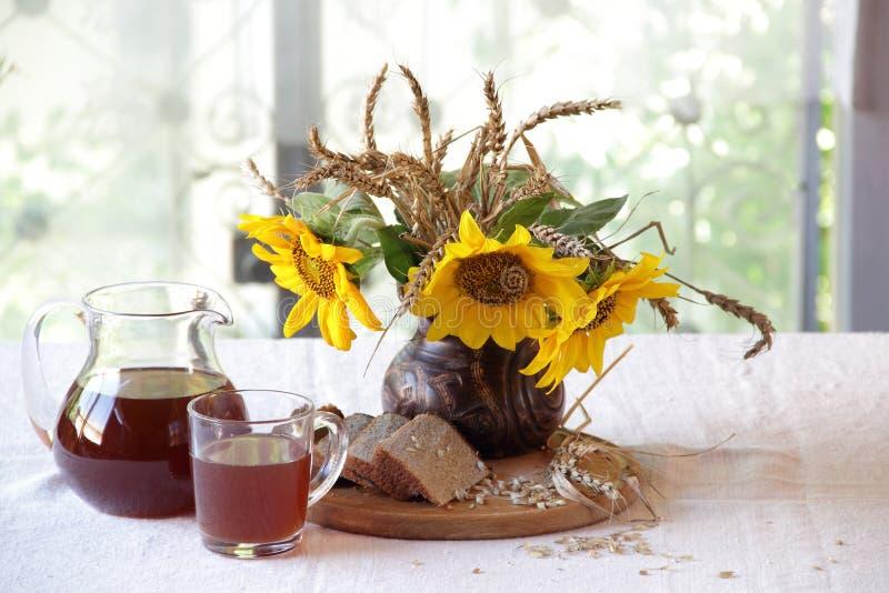 Stillleben mit Kwaß (kvas) und Sonnenblumen stockfotos