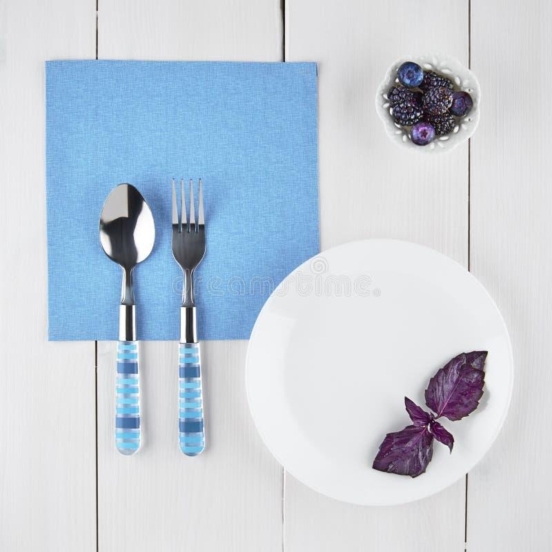 Stillleben mit Tischbesteck und Brombeeren auf hellen Brettern stockbild