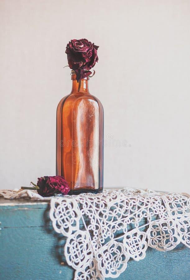 Stillleben mit trockenen roten Rosen in der Glasflasche auf dem Weinlesegummilack stockbilder