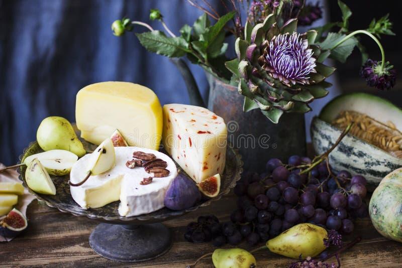 Stillleben mit unterschiedlichem Käse, frischen Früchten und Garten blüht lizenzfreie stockfotos