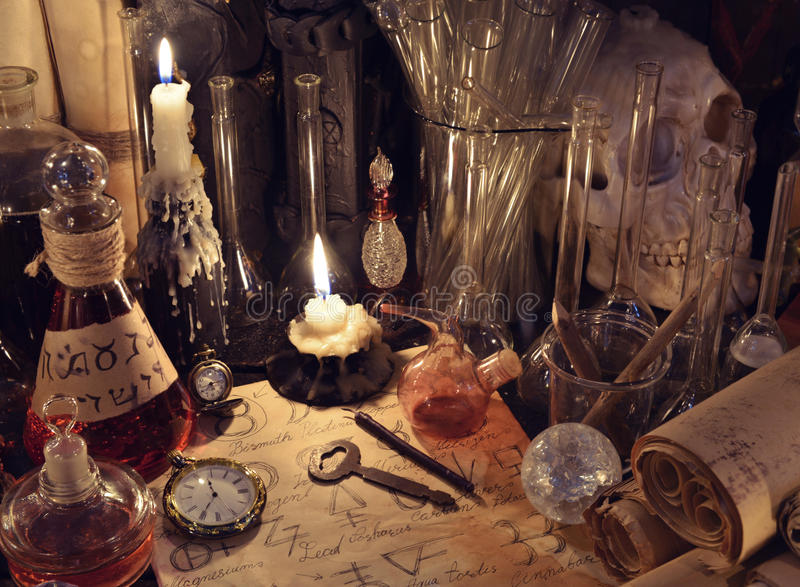 Stillleben mit Weinleseflaschen, magischen Gegenständen und Papier mit Alchimiezeichen stockfotografie