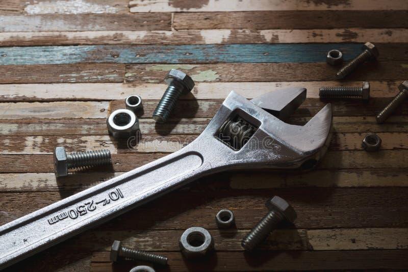 Stillleben nah oben von geschmiedetem justierbarem Schlüssel des Stahls, Nüsse - und - Bolzen auf hölzernem Plankenhintergrund stockbilder