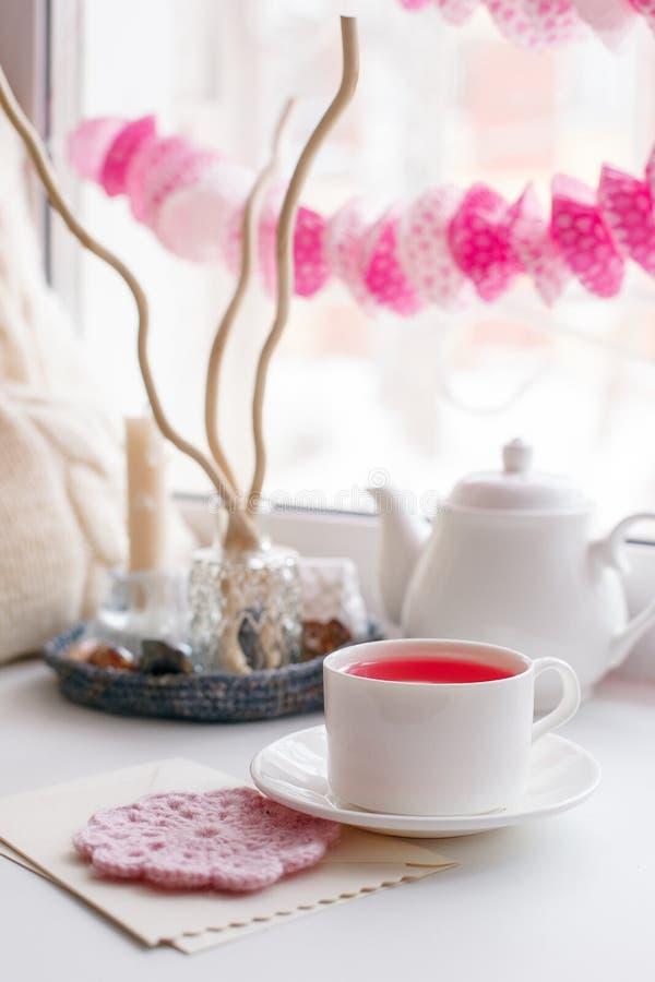 Stillleben von benutzten Kerzen, von Tee, von Teekanne, von Kissen und von rosa Papiergirlande auf einer weißen Tabelle nahe Fens stockfoto