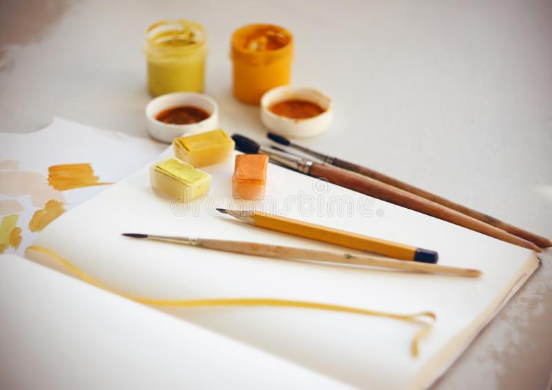 Stillleben von einem Sketchbook, auf dem eine Bürste und ein Bleistift und Farben sind lizenzfreie stockfotos