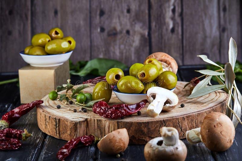 Stillleben von grünen neuen Oliven, von rotem Pfeffer und von frischen Pilzen mit Olivenbaumblättern auf einem dunklen hölzernen lizenzfreies stockfoto