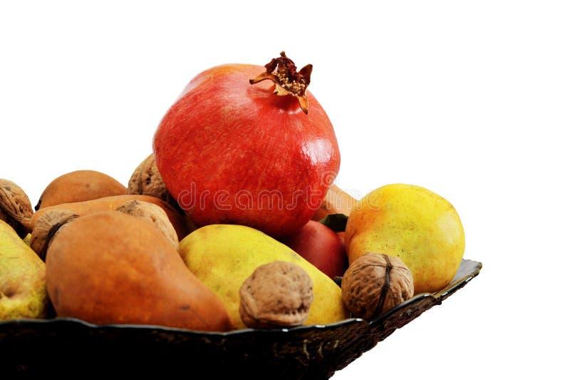 Stillleben von Granatäpfeln, von Äpfeln, von Birnen und von Nüssen in einem Vase auf dem weißen Hintergrund lokalisiert stockbilder