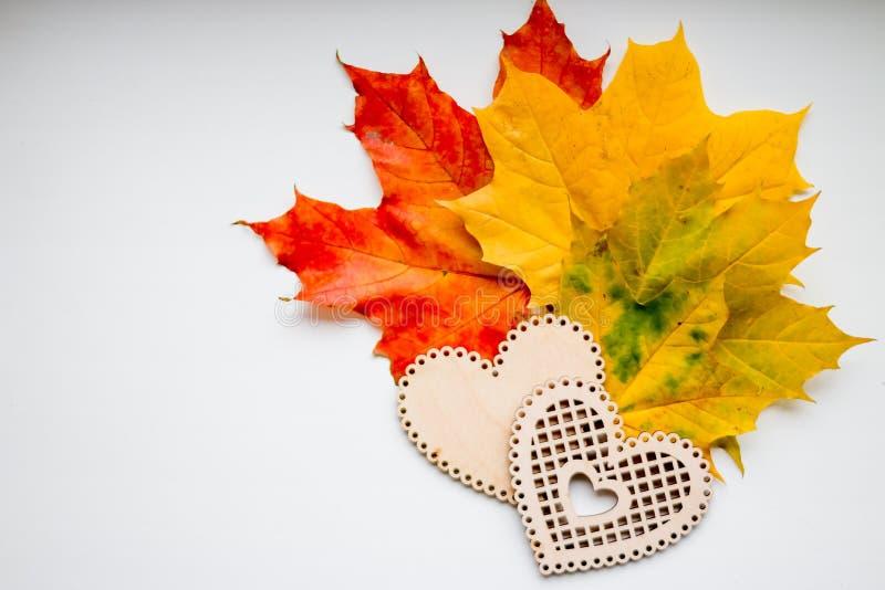 Stillleben von hölzernen Herzen und von bunten Blättern Herbststillleben, Kopienraum, dunkler Hintergrund, Herbstzusammensetzung lizenzfreie stockfotografie