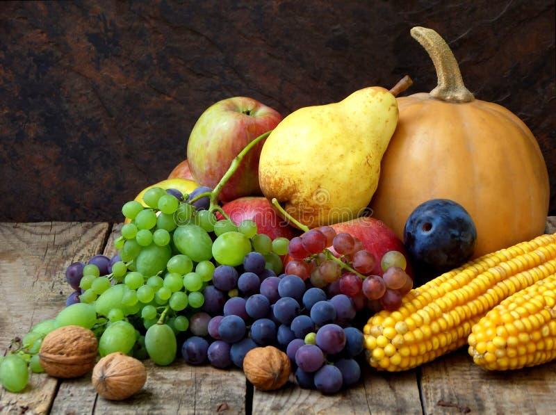 Stillleben von Herbstobst und gemüse -mögen Trauben, Äpfel, Birnen, Pflaumen, Kürbis, Maisnüsse lizenzfreies stockfoto