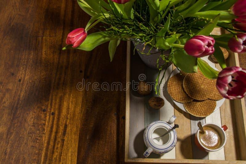 Stillleben von niederländischen Tulpen und von Sirup waffles auf einem Umhüllungsbehälter w lizenzfreies stockbild