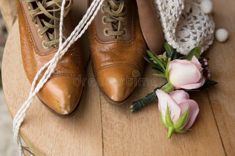 Stillleben von Stiefeln und von Blumen stockfotos