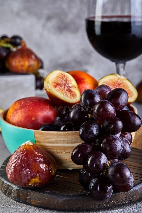 Stillleben von Trauben, von Pfirsichen, von Feigen und von Gläsern Rotwein auf einem Grau stockfoto
