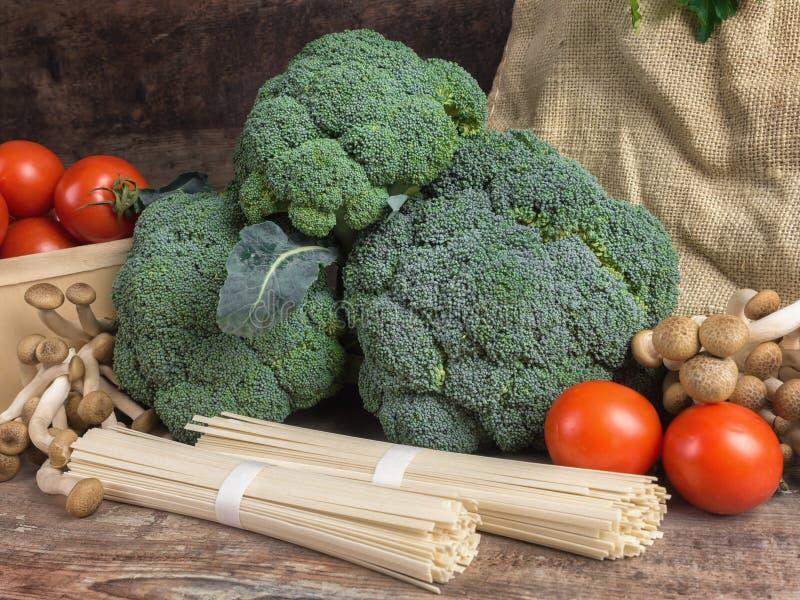 Stilllebengemüse-Kohlbrokkoli mit Tomaten vermehrt sich hölzerner Hintergrund der Spaghettigrün-Blätter explosionsartig stockfotos