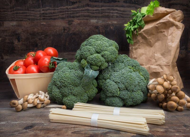 Stilllebengemüse-Kohlbrokkoli mit Tomaten vermehrt sich hölzerner Hintergrund der Spaghettigrün-Blätter explosionsartig lizenzfreie stockbilder