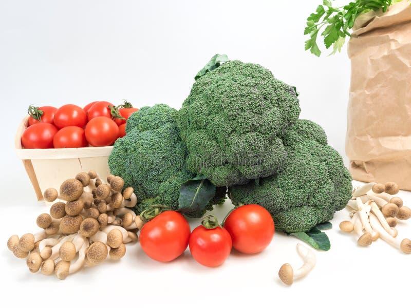 Stilllebengemüsekohl, den Brokkoli mit Tomaten grüne sich Blätter explosionsartig vermehrt, lokalisierte weißen Hintergrund stockfoto
