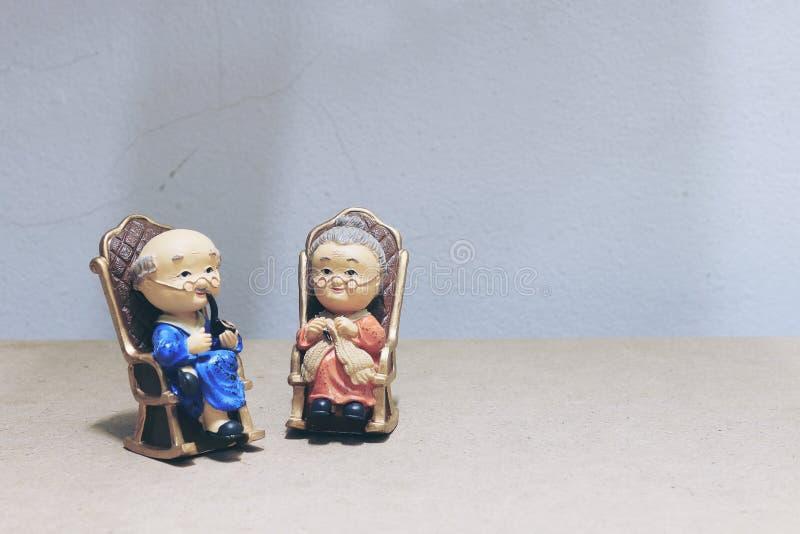 Stilllebenphotographie mit reizendem Großvater raucht und Großmutter mit der Katzenpuppe, die Schwingbambusstuhl mit Restlicht vo lizenzfreie stockbilder