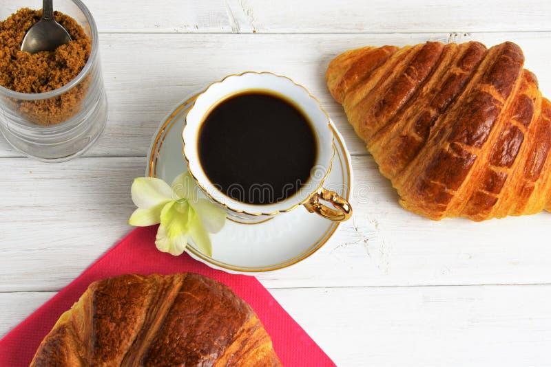 Stilllife der Kaffeetasse mit Espresso, Hörnchen, Kekse, zarte Blume, brauner Zucker auf einem hölzernen Hintergrund stockfoto