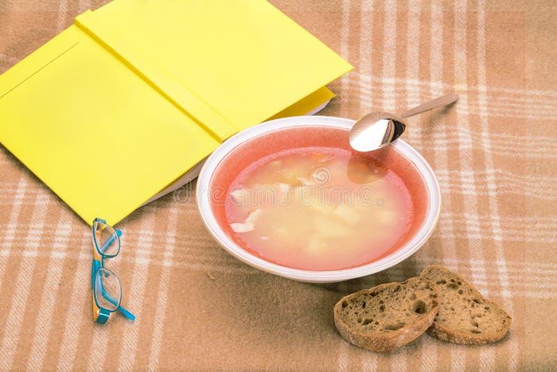Stilllife med den soppaplattan och boken royaltyfri foto