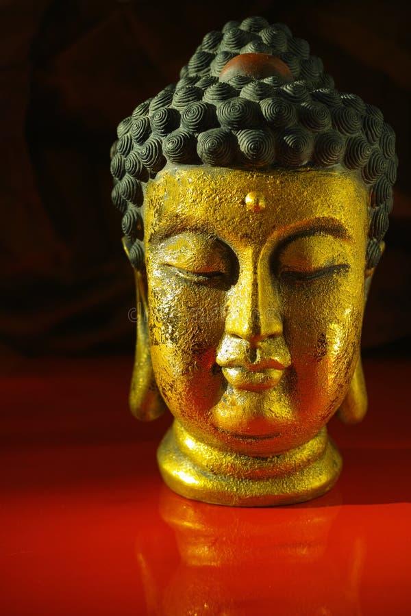 Stillsam framsida för guld- Buddha på mörker - röd bakgrund, kopieringsutrymme fotografering för bildbyråer