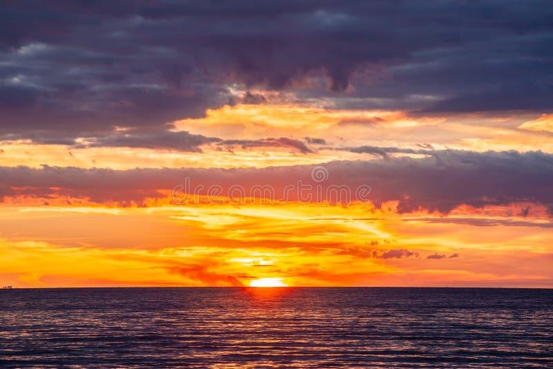 Stillsam livlig solnedgång med glödande orange moln royaltyfri bild