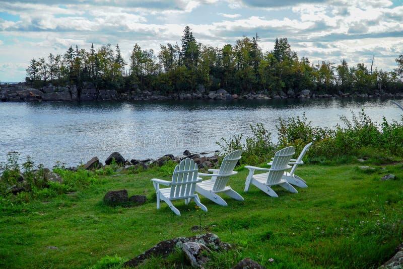 Stillsam plats med vita trägräsmattastolar på grönt gräs som förbiser Lake Superior i nordliga Minnesota royaltyfria bilder