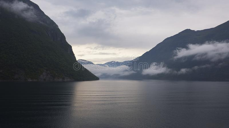 Stillsam sikt från det kalla ursprungliga fjordvattnet in mot de omgeende klipporna av Geirangerfjorden, Norge arkivbild