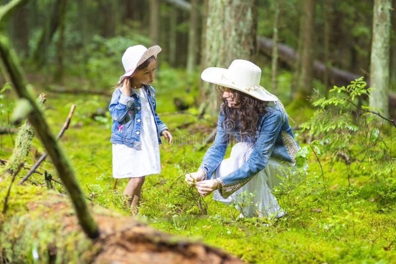 Stillsamma och positiva Caucasian par av modern och den lilla dottern som har Tid tillsammans i grön sommarskog fotografering för bildbyråer