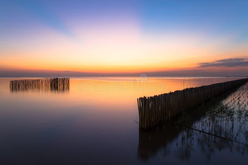 Stillsamt bildfoto av solnedgång- eller aftontid på havet eller havet på smällbajset Samutprakan, Thailand royaltyfri bild