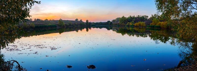 Stillsamt landskap för höst med det lilla dammet på solnedgången royaltyfri foto