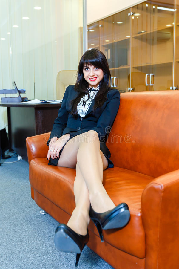 Stillstehendes Lügen der jungen schönen Geschäftsfrau auf einem Sofa im Büro lizenzfreie stockbilder