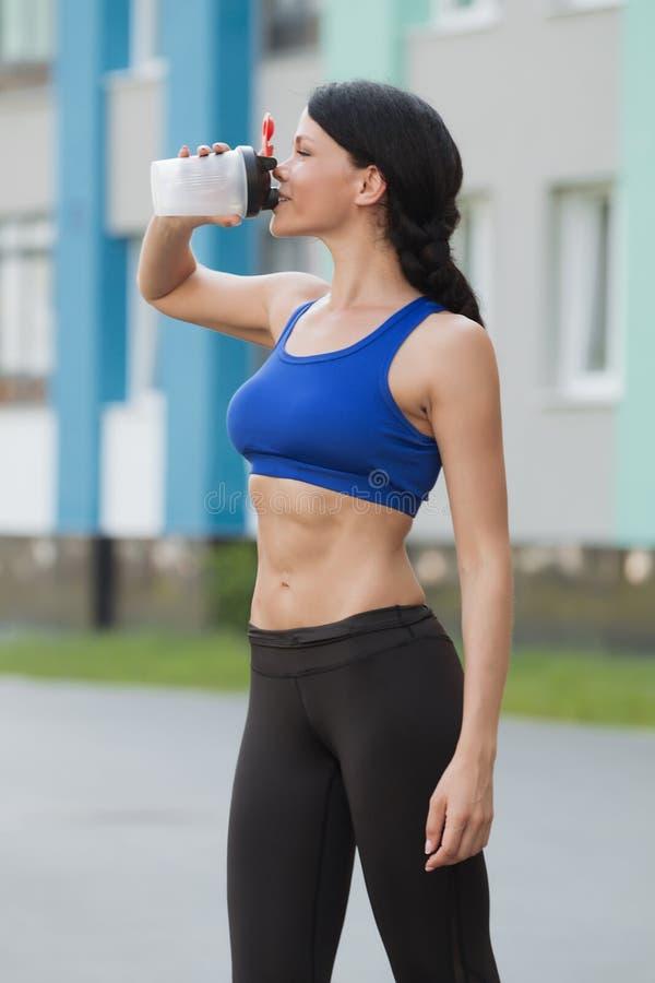 Stillstehendes Trinkwasser der schönen Eignungsathletenfrau nach arbeiten das Trainieren am Strandsommerabend im sonnigen Sonnens lizenzfreies stockfoto
