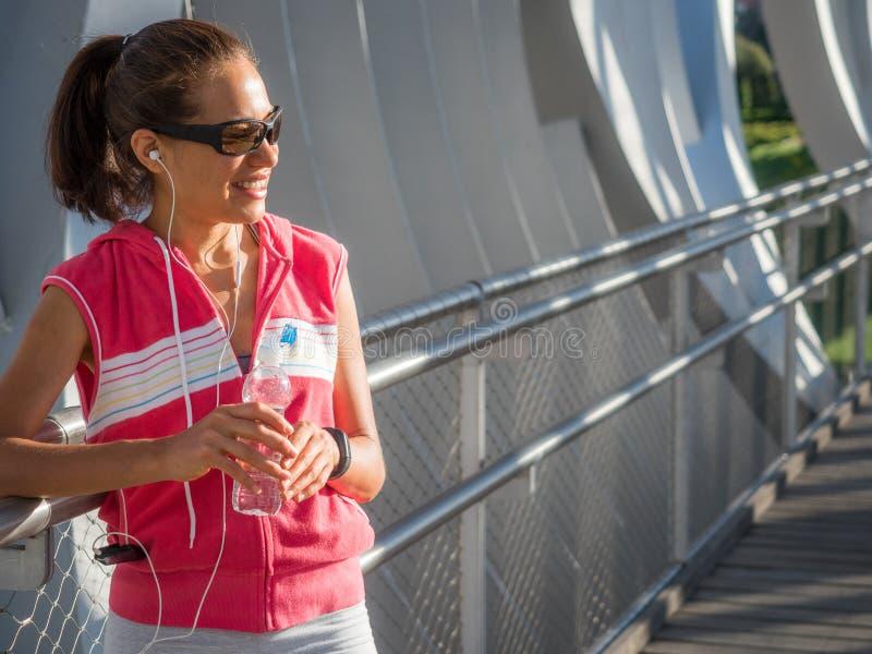 Stillstehendes und Trinkwasser des glücklichen weiblichen Läufers stockbild
