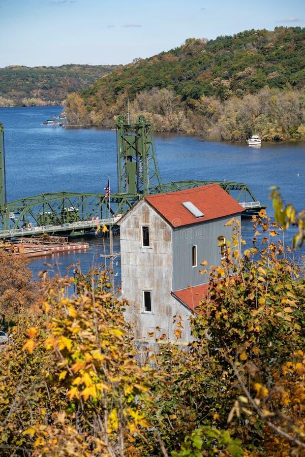 Stillwater, Minnesota i fall - förbiser en gammal fabrik med fallblad och hisbryggan på St Croix River royaltyfria foton