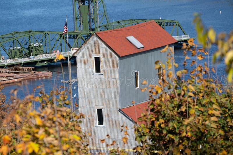 Stillwater, Minnesota jesienią - nad starym młynem z listkami opadającymi i mostem podnośnikowym na rzece St Croix zdjęcie royalty free