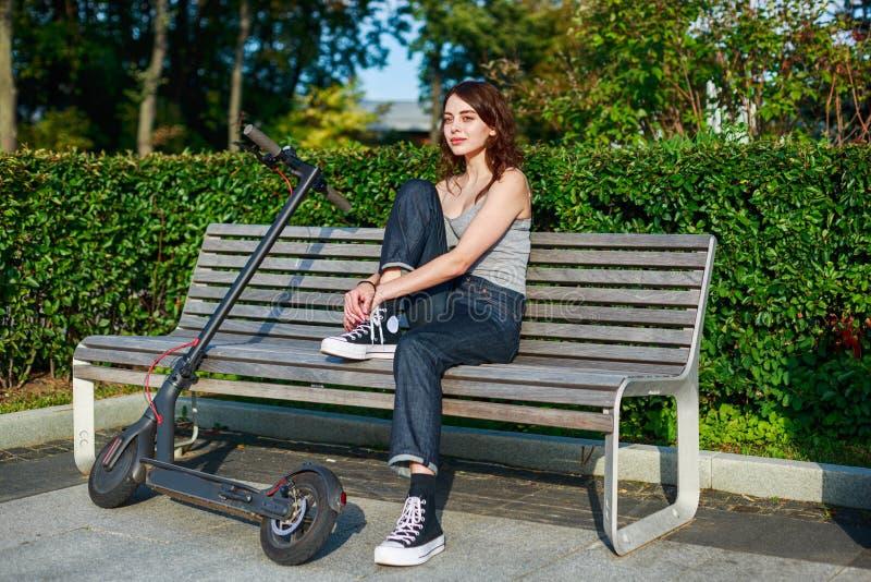 Stilmädchen sitzen zusammen mit ihrem E-Scooter draußen auf der Bank stockfotos