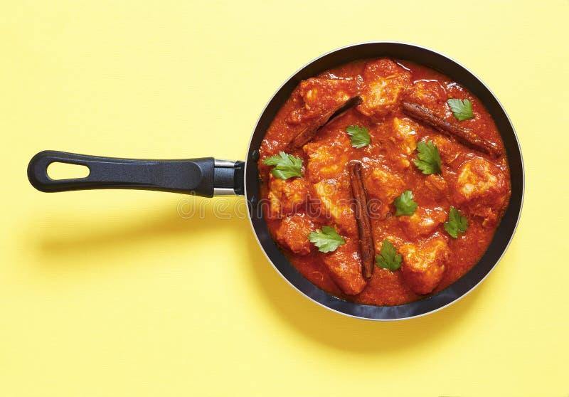 Stilminimalism Indisk mat Feg curry med kanelbruna pinnar, koriander och persilja i en stekpanna på en gul bakgrund arkivfoton